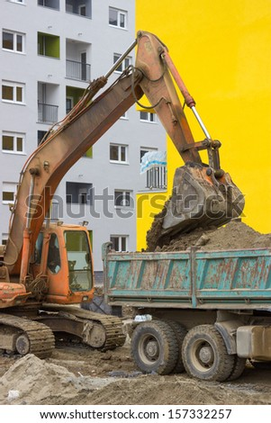 Excavator loading dumper truck at the building site - stock photo