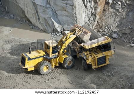 excavator loading granite stones in a quarry Cadalso de los Vidrios in Madrid, Spain - stock photo