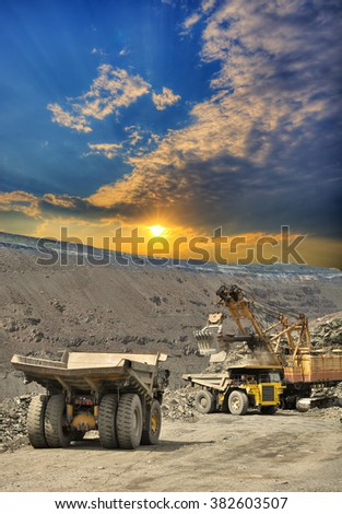 Excavator loading iron ore into heavy dump trucks on the opencast on sunset - stock photo