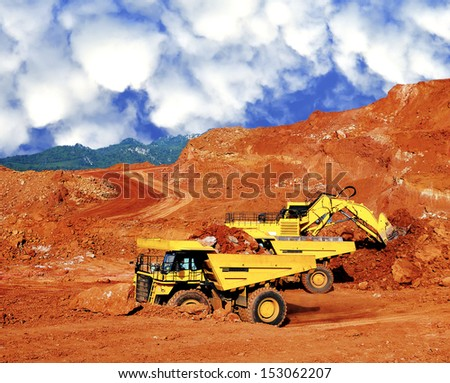 Excavator loading lignite stone in open pit mine - northern Thailand - stock photo