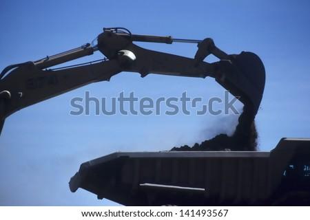 excavator loading ore into dump truck - stock photo
