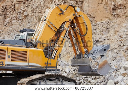 Excavator loading the crushed stone in quarry - stock photo