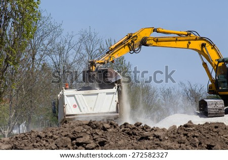 Excavator loading truck with gravel and dirt on the road construction site - stock photo