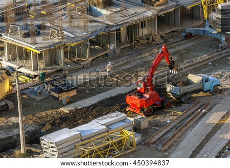Excavator loads the ground in the car at the construction site. - stock photo