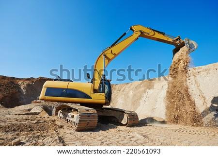 excavator machine at excavation earthmoving work in sand quarry - stock photo
