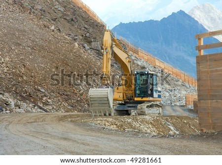 Excavator machine on a construction site in the mountains - stock photo