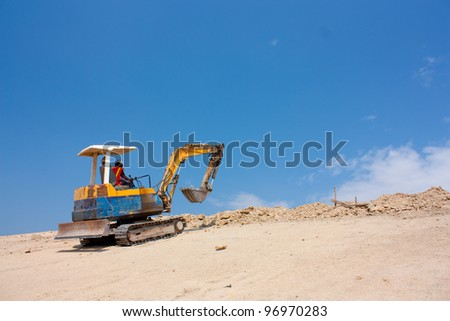 Excavator machine work on the earth mountain - stock photo