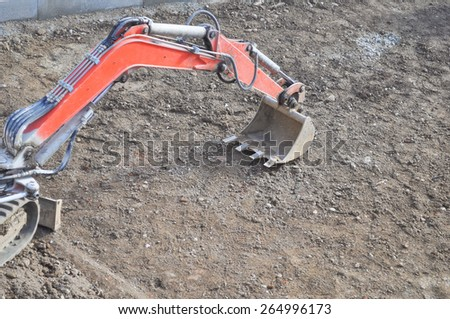 Excavator mechanical shovel digger digging a hole in the ground - stock photo