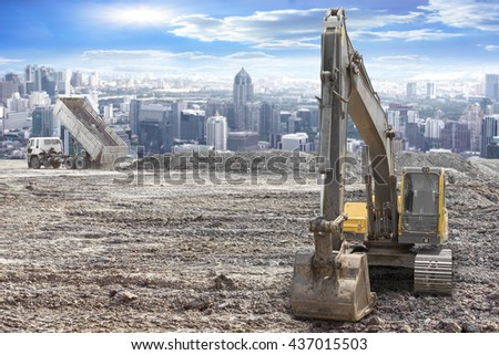 excavator on a construction site against urban scene - stock photo