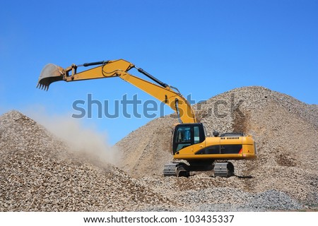 Excavator on a pile of rubble - stock photo