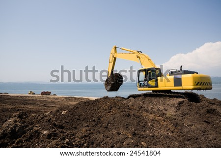 Excavator on the workplace on a background of the sea. - stock photo