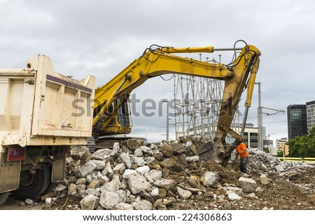 excavator placing sand or debris on a truck in Barcelona - stock photo