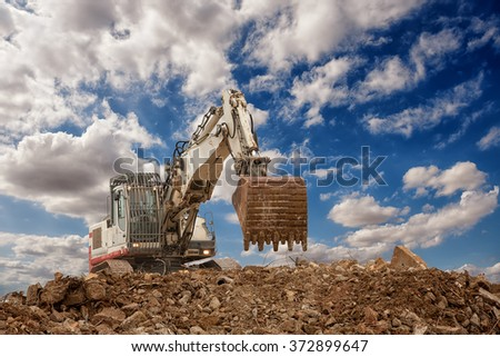 excavator with bucket on gravels blue cloudy sky background - stock photo