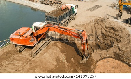 excavator working in the field - stock photo