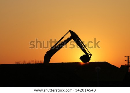 excavator working on construction site silhouette  - stock photo