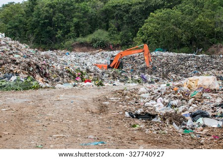 Excavators are management of garbage in the garbage dump.In thailand. - stock photo