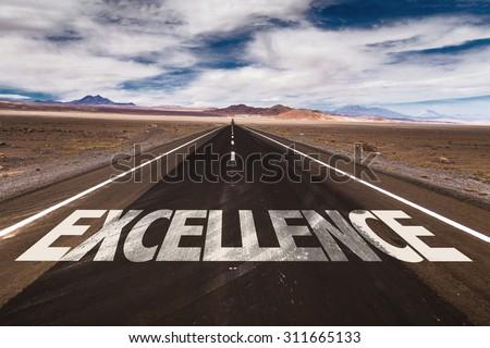 Excellence written on desert road - stock photo
