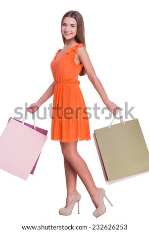 Excellent shopping. Full length of beautiful young woman carrying shopping bags and smiling while standing against white background   - stock photo