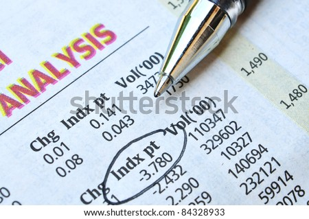 Exchange analysis on newspaper and pointing - stock photo