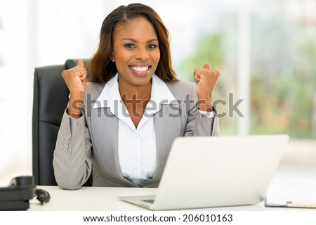 excited african american businesswoman waving fists in office - stock photo