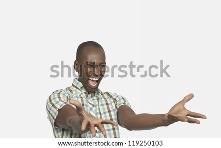 Excited African American man gesturing over white background - stock photo