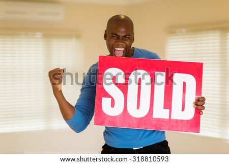 excited african man holding sold sign in his house - stock photo