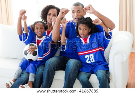 Excited Afro-American family watching a football match at home - stock photo