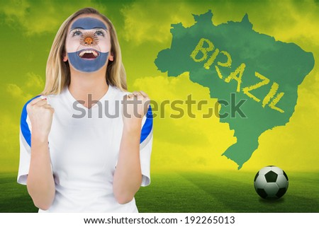 Excited argentina fan in face paint cheering against football pitch with brazil outline and text - stock photo