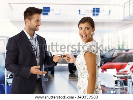 Excited attractive young caucasian lady is getting keys for new car from salesman at car dealership business saloon. Handsome man wearing suit and attractive woman, standing, looking at camera, - stock photo