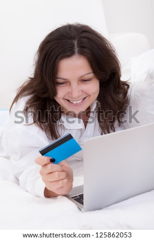 Excited attractive young woman lying on her bed with her laptop making purchases online with her credit card - stock photo