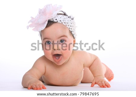 Excited baby girl lying on the floor isolated on white - stock photo