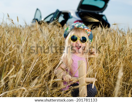 Excited beautiful little blond girl wearing a colorful hat and sunglasses playing with a wooden toy plane in a golden summer wheat field looking at the camera with her mouth open - stock photo