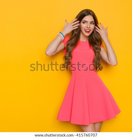 Excited beautiful young woman in pink mini dress  holding her long brown curly hair and looking away. Three quarter length studio shot on yellow background. - stock photo