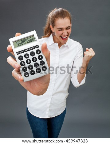 excited beautiful young woman laughing for her financial success, winning money in holding a symbolic calculator in the foreground - stock photo