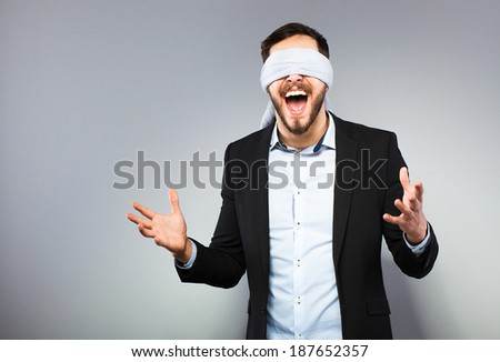 excited blindfolded man in black coat on grey background - stock photo