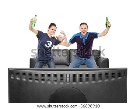 Excited boy and girl watching sport on a TV isolated on white background - stock photo