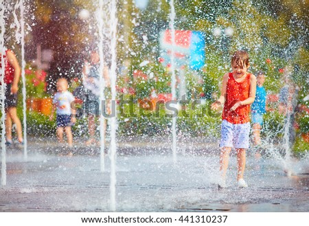 excited boy having fun between water splashes, in fountain. Summer in the city - stock photo
