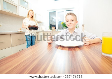 Excited boy sitting at the table waiting for dinner and playing with forks while his mother cooking in the kitchen - stock photo