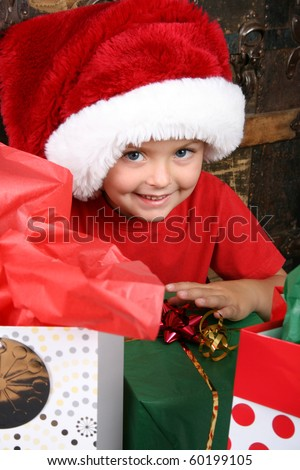 Excited boy waiting to open his Christmas presents - stock photo