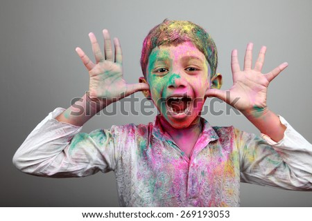 Excited boy with face smeared with colored powder. Concept for festival Holi - stock photo