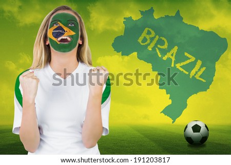 Excited brasil fan in face paint cheering against football pitch with brazil outline and text - stock photo