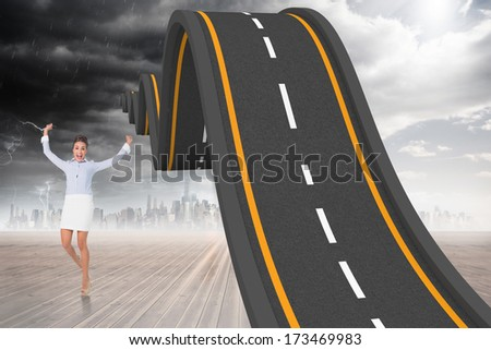 Excited brunette businesswoman jumping and cheering against city on the horizon - stock photo