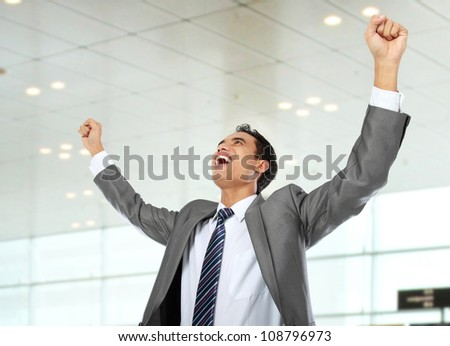 Excited business man celebrating success in the office - stock photo