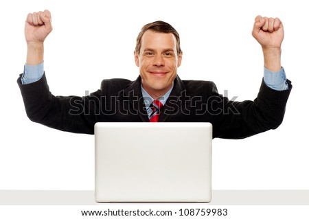 Excited businessman celebrating success with his arms raised up. Sitting in font of laptop - stock photo