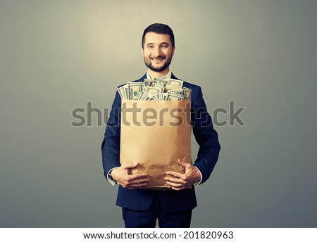 excited businessman holding paper bag with money and smiling. photo in studio over grey background - stock photo