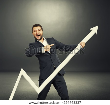 excited businessman pointing at white pointer and laughing. photo in the dark room - stock photo