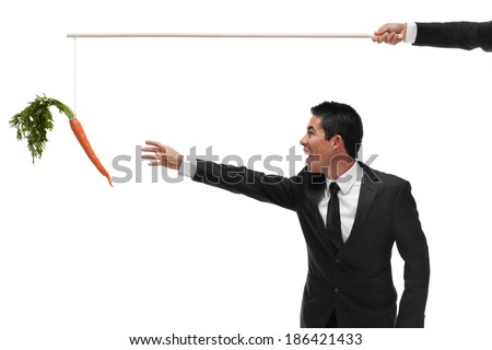 Excited businessman reaching for a carrot on the end of a stick being bribed - stock photo