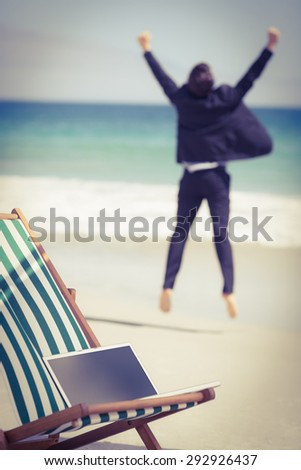 Excited businessman wearing a suit is jumping on the beach - stock photo