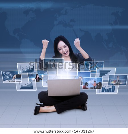 Excited businesswoman raised her arms looking at successful reports in laptop - stock photo