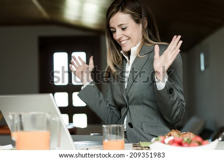 Excited businesswoman working at PC during breakfast - stock photo